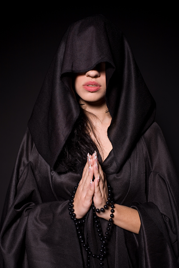 Praying nun in black hood isolated on black background